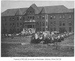 1907 Campus Day showing lunch tables in front of Clark Hall, University of Washington