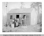 Family group outside small wooden building, including members of Van Olinda and Scott families,...