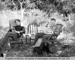 Howard Darlington and Frank Atkins reading outdoors, 1893