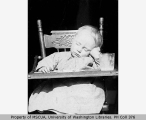 A. Eugene Van Olinda as a baby sleeping in high chair, probably Vashon Island, ca. 1903