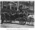 Visit to Seattle by Theodore Roosevelt shown seated in a carriage on 1st Ave., Pioneer Square...