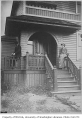 Warner family residence front entrance with two people and a cat  on the porch, Seattle, ca. 1900