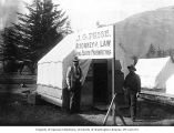 Two men in front of canvas-roofed building, with sign advertising J.G. Price, Attorney at Law,...