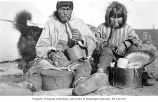 Eskimo couple, smoking pipes, seated beside carved wooden boxes and tools, location unknown, ca....