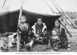 Eskimo family, possibly Siberian, seated in front of cloth shelter with fur floor covering,...