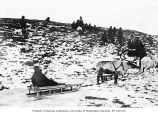 Group of Native Americans, one seated on sled pulled by reindeer, location unknown, ca. 1899