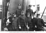 Crew posing for group portrait on board ship, one holding small dog, location unknown, ca. 1899