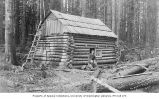 Man seated outside of log house, Sedro Woolley, ca. 1894