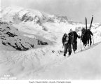 Members of the SOYP club hiking up slope with snowshoes and skiis, Mt. Rainier National Park, 1925