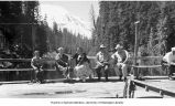 Group posing on lodge bench with Mt. St. Helens and Spirit Lake in background, ca. 1950