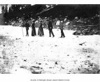 Hikers with walking sticks crossing over snow in Paradise Valley, Mount Rainier National Park,...
