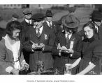 Two women pouring cider from pitchers and two newspaper reporters taking notes, October 1920
