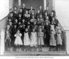 Students standing with teacher A.S. Burrows on the front steps of the two-room school house at...