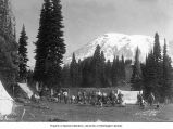 Mountaineers and campers in tent encampment at Paradise Park with climbing equipment, showing...