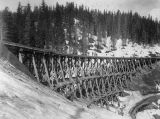 Men standing on large Northern Pacific Railway trestle during winter, Washington, ca. 1887
