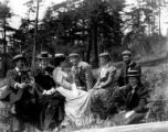 Group of men and women sitting outdoors, May 30, 1898