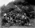 Group of people sitting on grass with dog, June 24, 1899