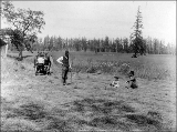 A.W. Bash and daughter Cora Clementine seated in timothy field watching a man driving a harvester,...