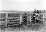 A.W. Bash and daughter Cora Clementine and man viewing oat field in salt marsh area on the Bash...
