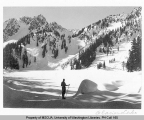 Skier on frozen Glacier Lake with view of Surprise Pass and Surprise Peak, n.d.