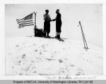 Two skiers atop the summit of Mt. Baker standing next to a U.S. flag, n.d.