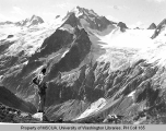 Hiker viewing Dome Peak and the west fork of the Agnes River probably from Lizard Mountain, 1938