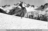 Hiker walking on South Cascade Glacier with view of Dome Peak and Sinister Peak, 1939