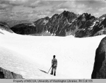 Hiker standing on ice field of South Cascade Glacier looking toward Le Conte Mountain, 1938