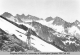 Hiker on a glacier overlooking Spire Peak, ca. 1938