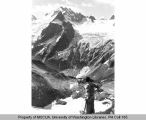 Hiker on a ridge above White Rock Lake and South Cascade Glacier with view of Dome Peak, 1938