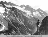 Hiker standing on a ridge overlooking the head of Downey Creek with view of Spire Peak, 1938