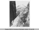 Mountaineer scaling a cliff with Sahale Peak in background, n.d.