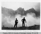 Two hikers looking across a misty valley at Johannesburg Mountain, Cascade Pass, n.d.