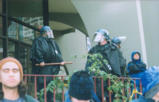 Three cops in riot gear on a balcony, downtown Seattle
