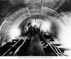 Men sealing the main tunnel between the outlet flume and the forebay with a grouting machine, May...