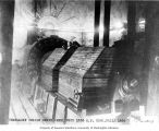 Power house interior showing Pelton water wheel in underground chamber, 1900