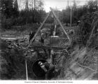 Installing pipe in trench underneath the Black River, ca. 1899
