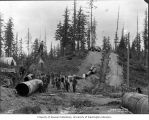 Men using pulleys to lay steel pipe near Dunlap Canyon south of Seattle, ca. 1899