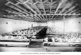 Interior of dining hall for construction workers, with tables set for meal and numbered seats,...