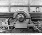 Man posed next to turbine water wheel in powerhouse, with pressure regulators to the right, n.d.