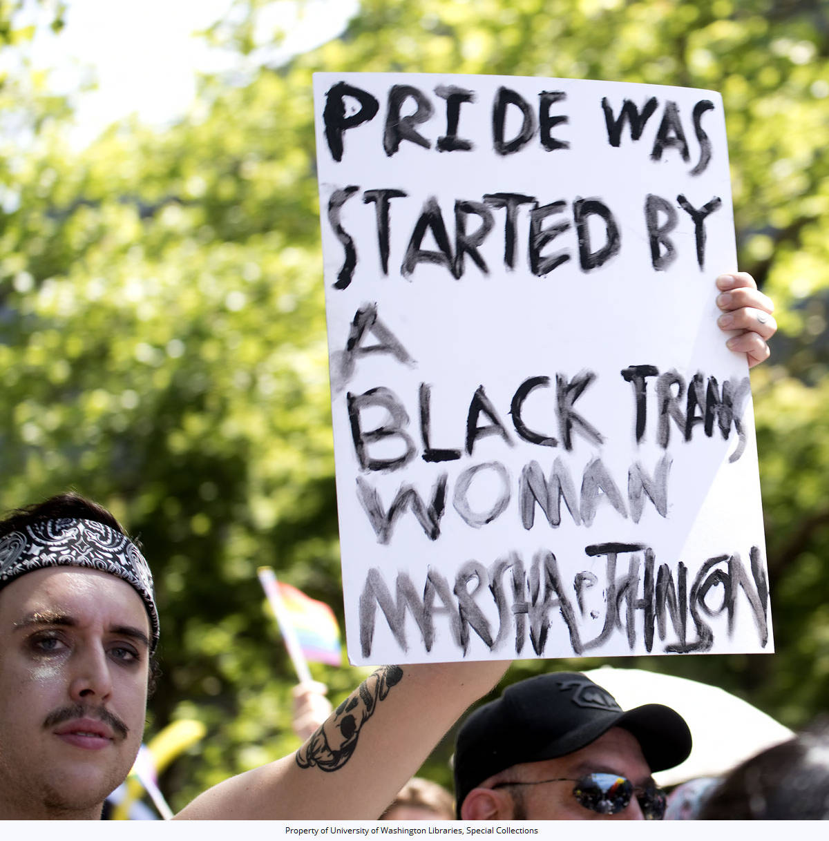 """43rd Annual Pride Parade: Marcher holding a sign reading """"Pride was started by a black trans woman - Marsha Johnson"""", Denny Way at 2nd Ave N., Seattle, Washington, June 25, 2017"""
